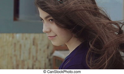 Portrait of the young girl with waving long hair looking at camera. Slowly