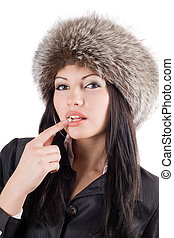 Portrait of the young woman in a fur cap. Isolated on white