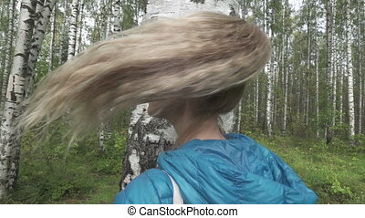Portrait of the young woman with a long fair hair in the birch wood,slow motion