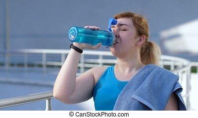 Portrait of thirsty female runner drinking water