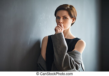 Portrait of thoughtful beautiful woman on dark background