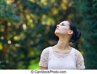 Portrait of thoughtful girl in woods looking on copy space