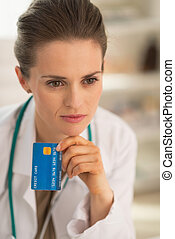 Portrait of thoughtful medical doctor woman with credit card