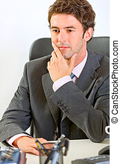 Portrait of thoughtful modern businessman in office