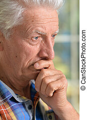thoughtful senior man with hand on chin