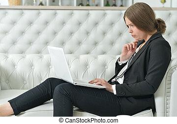 Portrait of thoughtful teen girl wearing formal wear using...