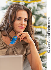 Portrait of thoughtful young woman with credit card and laptop near christmas tree