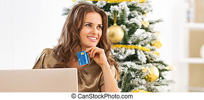 Portrait of thoughtful young woman with credit card using laptop near christmas tree