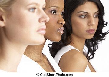 Portrait Of Three Attractive Young Women In Studio Standing...