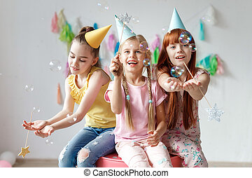 Portrait of three beautiful girls wear festive caps, play with bubbles, sit together on chair, celebrate birthday, being in good mood, use magic wand, have party in decorated room. Childhood concept.