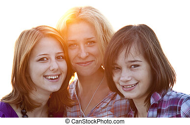 Portrait of three beautiful girls. With counter light on background.
