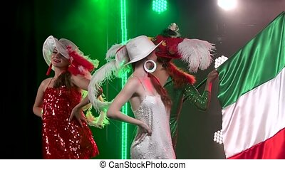 Portrait of three charming women posing in the rays of bright lights with the flag of Italy. Theatrical show close up. Slow motion