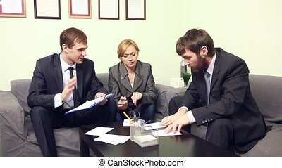three co-workers discussing business plan in office. -...