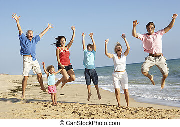 Portrait Of Three Generation Family On Beach Holiday Jumping...