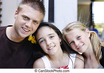Portrait of three happy adolescents together outdoors - A...