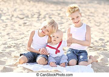 portrait of three little boys on the beach in summer