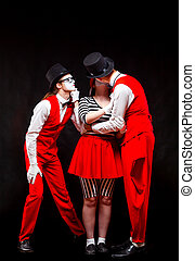 Portrait of three mime artists, isolated on black background...