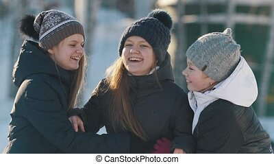 Portrait of three teenage girls playing and tickling each other in winter outside