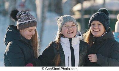 Portrait of three teenage girls posing, hugging and smiling...