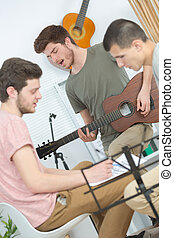 portrait of three trendy teenagers playing music