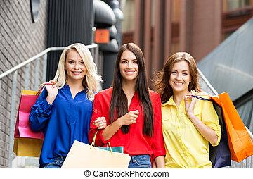 Portrait of three young happy beautiful women on street...