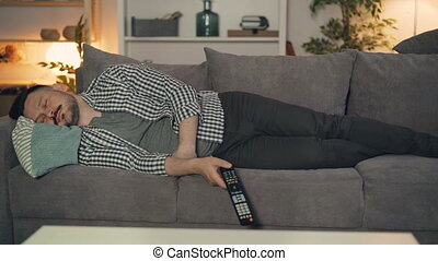 Portrait of tired person sleeping on couch alone holding TV...