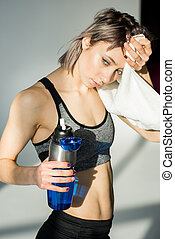 tired sporty woman holding bottle with water