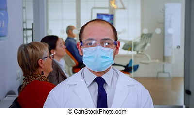 Portrait of tired stomatologist wearing protective mask at camera being in dental office while patients waiting him in background. Dentist looking on webcam sitting on chair in stomatological clinic.