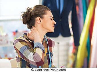 Portrait of tired tailor woman with neck pain