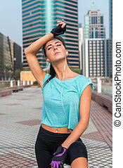Portrait of tired young fitness woman taking a break from working-out, wiping sweat from her forehead, listening to music. Female athlete resting after exercising outdoors on city street