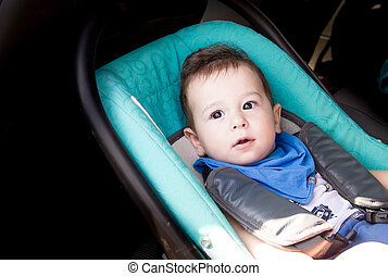 Portrait of toddler boy in car seat. Little smiling baby child fastened with a seat belt portrait of adorable happy baby boy sitting in the car seat. concept in safety in the car.