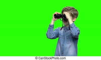Portrait of tourist boy in denim jacket using binoculars....