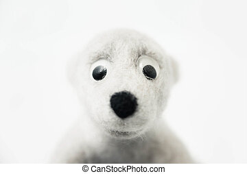 portrait of toy polar bear made of felted wool on white background