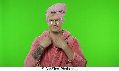 Portrait of transsexual man in bathrobe looking in mirror ...