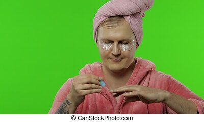 Portrait of transsexual man in bathrobe painting his hand ...