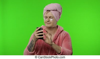 Portrait of transsexual man in bathrobe using mobile phone ...