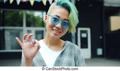 Portrait of trendy Asian girl showing OK hand gesture and...