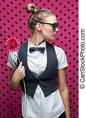 Portrait of trendy girl with ponytail hairstyle and pink flower