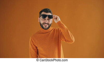 Portrait of trendy guy raising sunglasses and smiling...