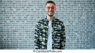 Portrait of trendy guy taking off sunglasses and smiling looking at camera standing against brick wall background. Modern young people, style and emotions concept.
