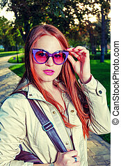 Portrait of Trendy Redhair Girl Standing in the park lane. Urban Fashion Concept  Red Lips and funny sunglasses.  Toned Color. Chic Long Hair. Colorized
