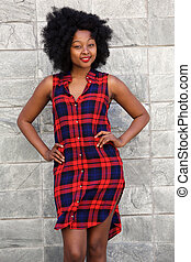trendy young woman standing in plaid dress