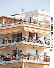 Portrait of tropical apartment building with balconies.