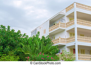 Portrait of tropical apartment building with trees.