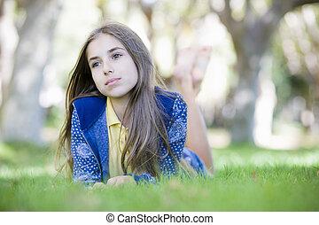 Portrait of Tween Girl Lying on Grass looking away from...