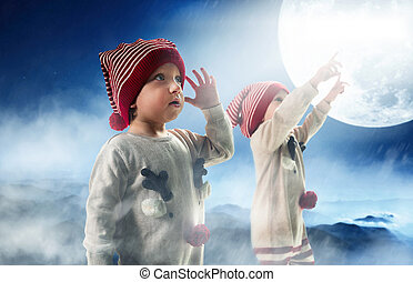 Portrait of two adorbale twin brothers looking at the Christmas sky