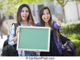 Portrait of Two Attractive Mixed Race Female Students Holding Blank Chalkboard with Thumbs Up and Carrying Backpacks on School Campus.