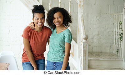 Portrait of two beautiful african american girls laughing and looking into camera at home