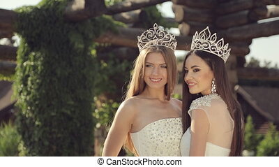 Portrait of two beautiful girls in wedding dresses and tiaras outdoors in a park