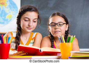 Portrait of two beautiful schoolgirl in classroom